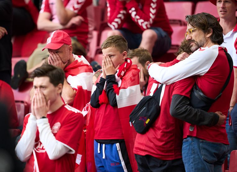 Deens fans in shock na de hartstilstand van Christian Eriksen afgelopen zaterdag tijdens de wedstrijd Denemarken-Finland op het EK voetbal. Beeld FrontzoneSport via Getty Images
