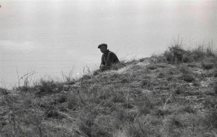 Pieter Kuijt zittend in de duinpan.  Beeld NIOD