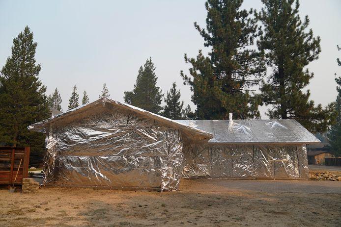 Een met folie ingepakt huis in Meyers, Californië, kan de bosbranden in het gebied doorstaan.