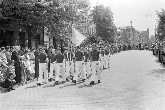 Intocht van de wandelaars in de Molenstraat, tijdens de ' Oss Voorwaarts'-wandeltocht op 11 mei 1952. Op de achtergrond de gesloopte Koekfabriek en Paterskerk.
