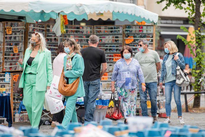 Bezoekers van de markt van Antwerpen dragen mondkapjes. Er geldt een mondkapjesplicht op alle markten.