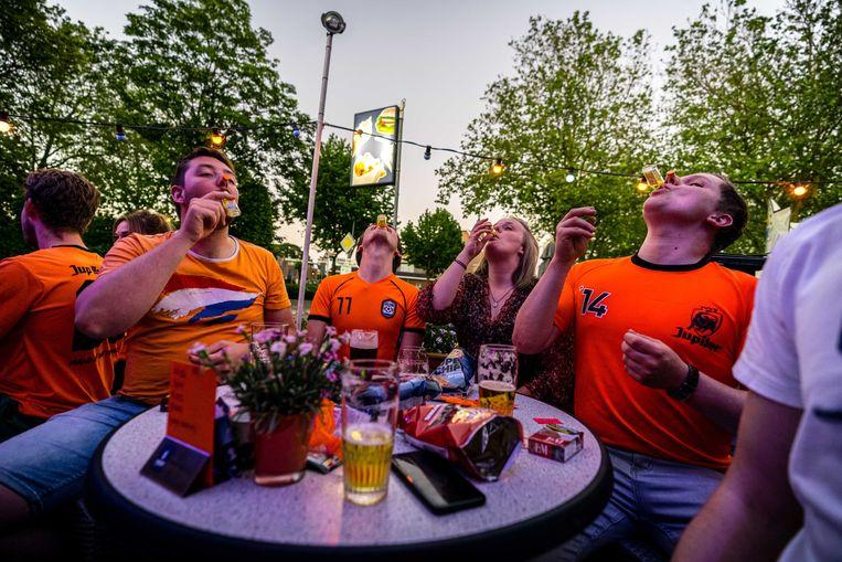 Voetbalsupporters volgen op een scherm het EK voetbal tussen Nederland en Oekraïne in een cafe in België. In het buurland mag een flinke groep op grote schermen het EK bekijken. Beeld ROB ENGELAAR/ANP