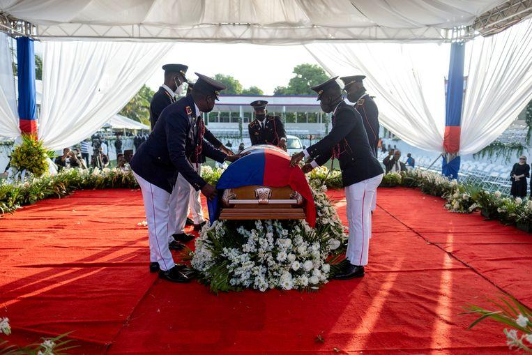 Een presidentiële erewacht drapeert de nationale vlag over de kist van de vermoorde Haïtiaanse president Jovenel Moïse tijdens zijn begrafenis op 23 juli. Beeld REUTERS
