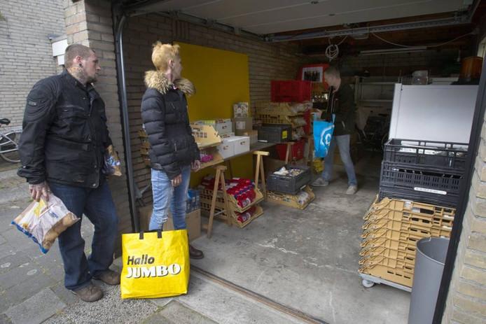 Patrick Verkoelen (rechts) vult op zaterdagochtend boodschappentassen voor Angelo en Jessica Vogels.