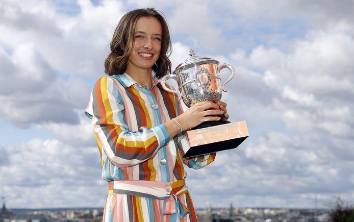 Iga Swiatek poseert met de trofee van Roland Garros. Ze is de eerste Poolse winnares van een grand slam ooit.