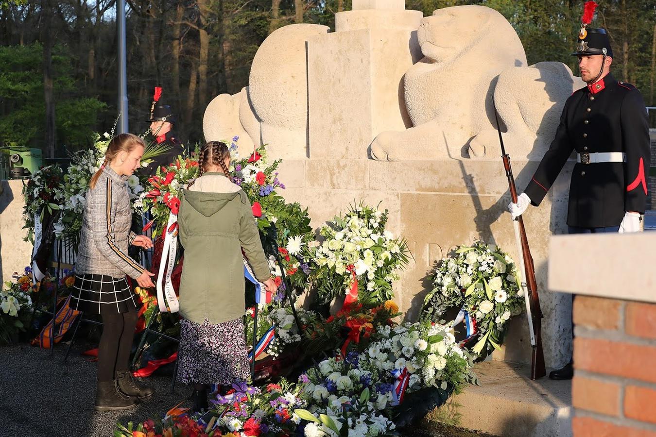 Schoolkinderen leggen bloemen bij het monument op de Grebbeberg.