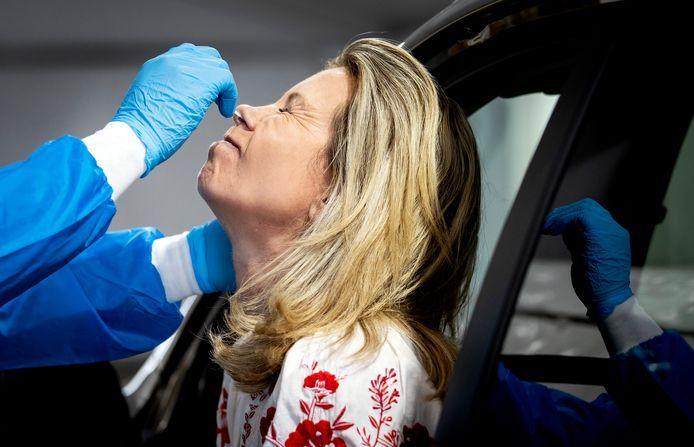 Een medewerker van de GGD Rotterdam-Rijnmond neemt een coronatest af in een teststraat.