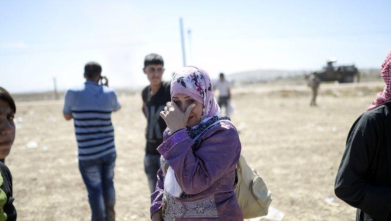 Een Syrisch-Koerdische vrouw huilt nadat ze vanuit Syrië de Turkse grens is gepasseerd. Beeld afp