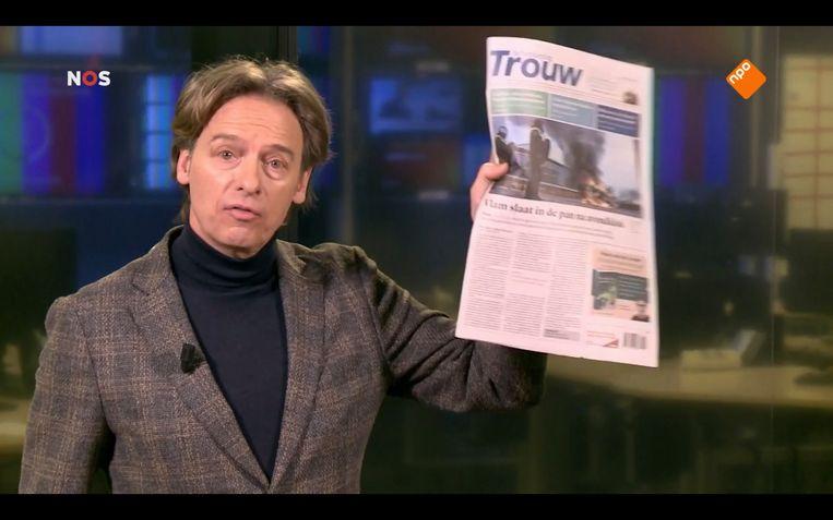 NOS-verslaggever Kees van Dam met een editie van Trouw in zijn handen. Beeld