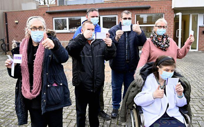 Het bewijs in de hand: deze blije bewoners van De Kerselaar tonen hun vaccinatiekaartje.