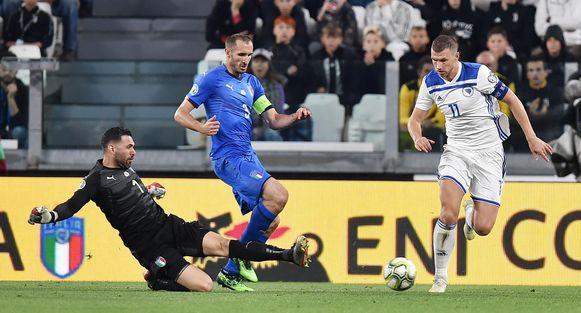 Edin Dzeko (r) in actie tijdens de EK-kwalificatiewedstrijd tegen Italië.