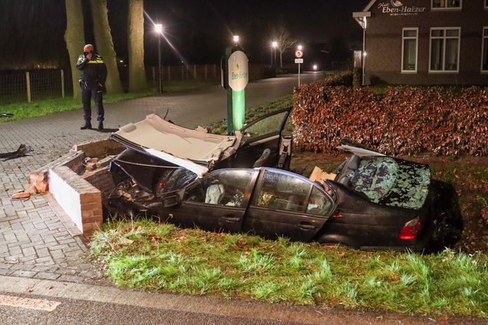 De zwaar gehavende BMW in de sloot tegen de duiker in Lunteren nadat de bestuurder eruit is gered.