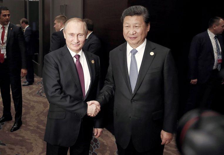 De Chinese president Xi Jinping (R) schudt handen met de Russische president Vladimir Putin. Beeld afp
