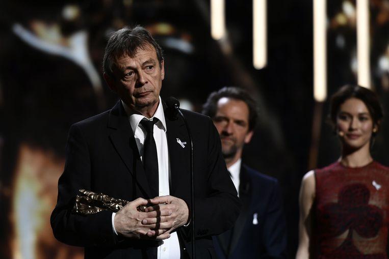 De Franse schrijver Pierre Lemaitre met de Best Adaptation award voor de film 'Au revoir la-haut' tijdens de Cesar Awards in Parijs op 2 maart 2018.  / AFP PHOTO / Philippe LOPEZ