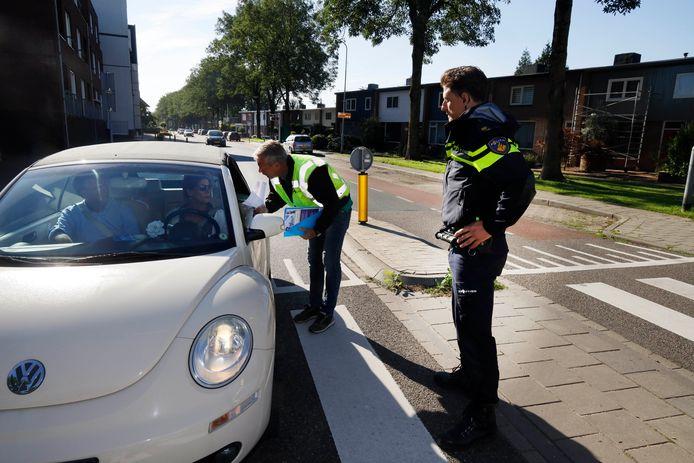 Een automobilist wordt nadat hij op de Burgemeester Geradtslaan in Beuningen staande is gehouden een flyer uitgereikt. Daarop vraagt de politie mensen die meer weten over het schietincident dat er vorige week maandag plaatshad, zich te melden.