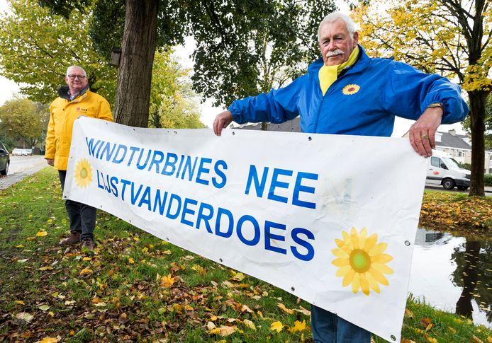 Lokale politici Hendrie van Assem (links) en Jaap van der Does met het spandoek tegen windturbines. Zo'n spandoek hing ook langs de Molenvlietbaan, maar die is ontvreemd. Thuis had Van der Does nog een exemplaar liggen.