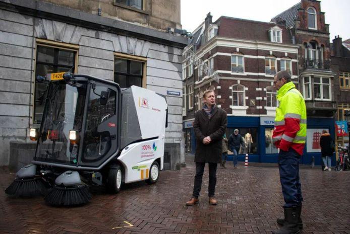 Wethouder Kees Diepeveen (GroenLinks) bij de jongste aanwinst van de gemeente: een veegwagen die op groene waterstof door de binnenstad rijdt.