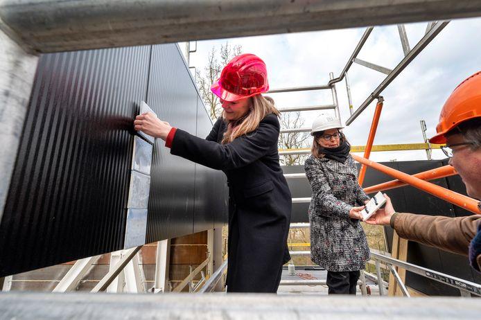 Wethouder Cathelijne Bouwkamp (l) en museumdirecteur Saskia Bak (m) zetten de eerste tegels tegen de buitengevel van de nieuwe vleugel van Museum Arnhem. Directeur Egbert Jan Rots (r) van aannemer Rots Bouw reikt de tegels aan.