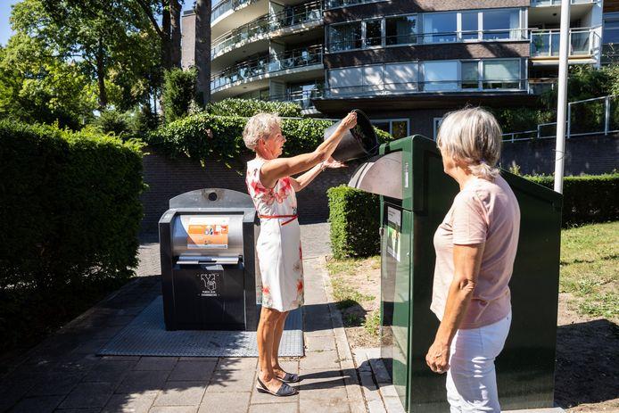 Coby Timmerman kiepert een emmertje gft-afval in de groene gft-container bij haar appartement in de Burgemeesterswijk in Arnhem-Noord. Rechts bewoonster Ans Stokman.