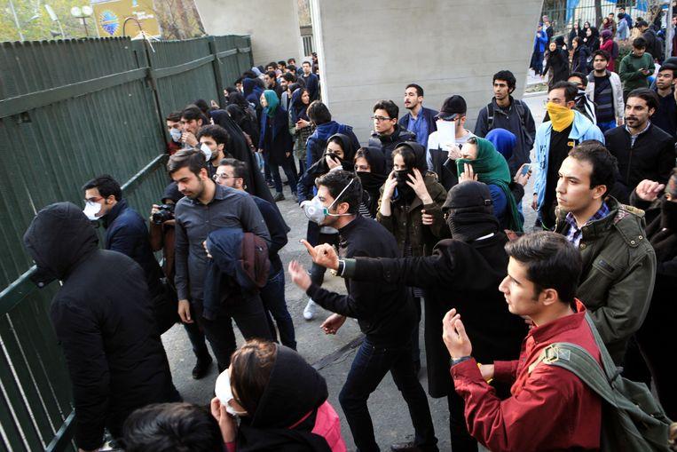 Iraanse studenten zaterdag tijdens een confrontatie met de politie in Teheran.  De afgelopen drie dagen is op verschillende plekken in Iran gedemonstreerd tegen de regering. Beeld EPA