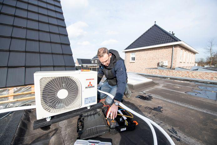 Dolf Romp van Kamphuis Koeltechniek BV uit Hengelo monteert een airco bij Jos en Astrid Vogelzang uit Almelo.