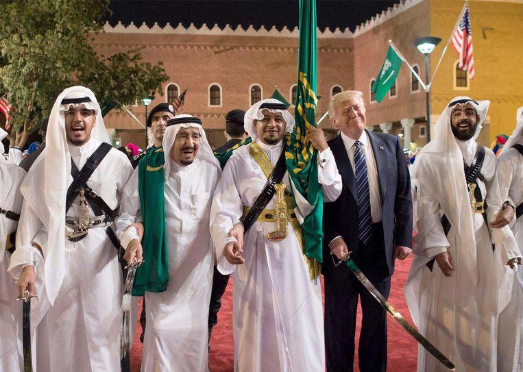 Amerikaans president Donald Trump en Saudisch koning Salman bin Abdulaziz Al Saud tijdens een welkomstceremonie met traditionele zwaarddansers in Riyad. Beeld EPA