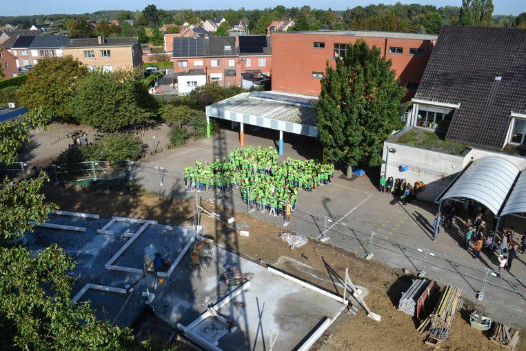 De leerlingen van basisschool Gavertje Vier vormen een groot klavertje vier, naast de werf waar stilaan de nieuwbouw verijst voor de uitbreiding van de school en de kinderopvang.