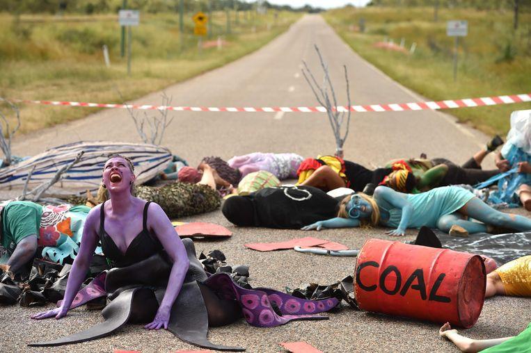 Australische milieu-activisten bij een protest in mei van dit jaar tegen het omstreden Adani-kolenmijnproject nabij Bowen, Queensland, waar de terminal moet komen om de steenkool over te slagen op schepen. Beeld AFP