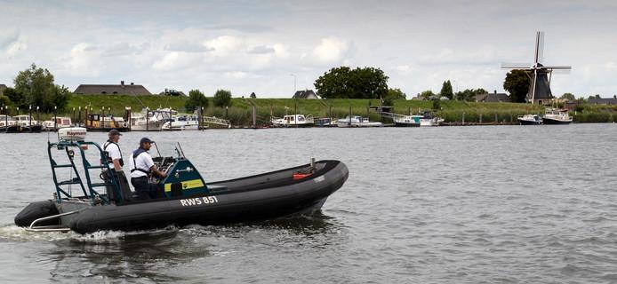 Tjeerd Zijlstra en Ron Duijndam zijn in hun ribboot, hier bij Nederhemert, iets te herkenbaar voor watersporters. Sommigen maken zich uit de voeten zodra de zwart-gele boot in zicht komt.