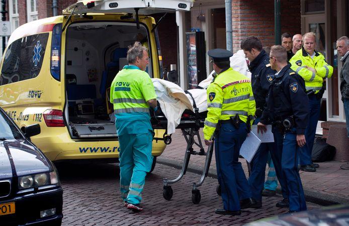 Het slachtoffer van de overval op juwelier Sylvia Mosterd aan de Hofstraat wordt afgevoerd door ambulancepersoneel.