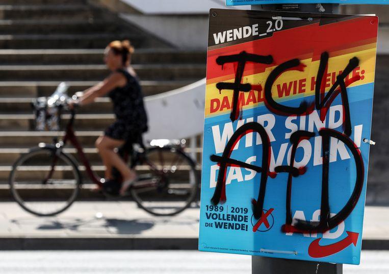 Een vrouw fietst langs een besmeurde verkiezingsfoto van Alternative Für Deutschland in Potsdam. Beeld EPA