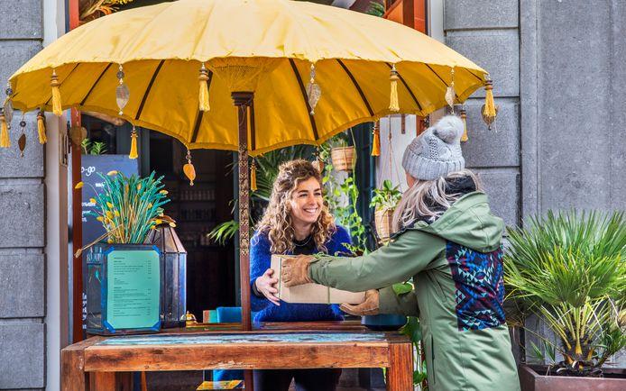 Onder de gele parasol geeft Ellen Kruidhof een dinerbox mee.