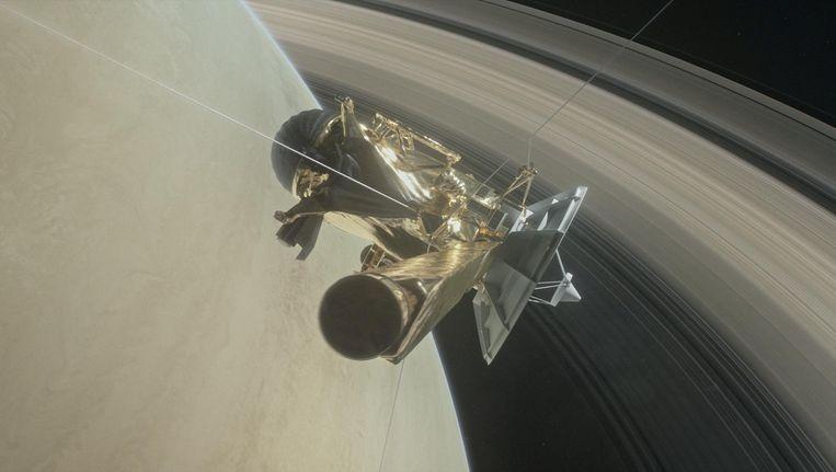 Een illustratie van ruimtesonde Cassini tussen Saturnus en de ringen rond de planeet. Beeld REUTERS