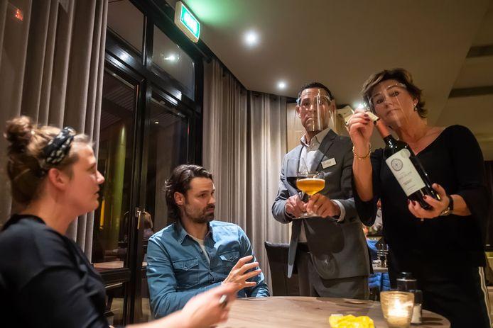 Maja van der Made (R) pakt de wijn van tafel en stopt de kurk terug in de fles. Fadi haalt de glazen van tafel.
