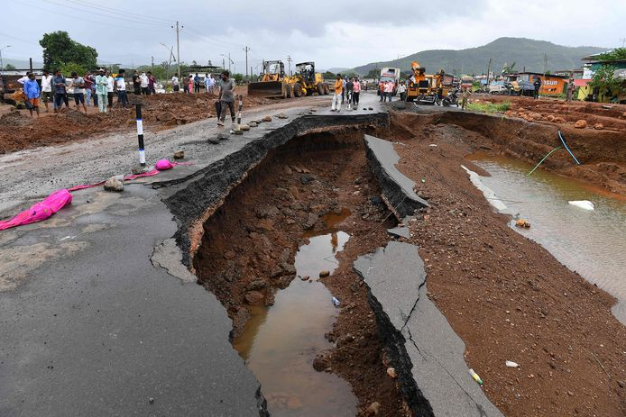 People gather along a section of highway partially washed away from the rain at Mahad on July 24, 2021, as the death toll from heavy monsoon rains climbed to 79, with nearly 100,000 others evacuated in the western state of Maharashtra. (Photo by INDRANIL MUKHERJEE / AFP)
