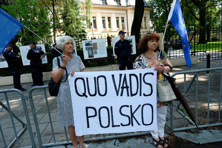 Demonstranten staan voor een zitting van het Grondwettelijk Hof in Warschau. Beeld Reuters