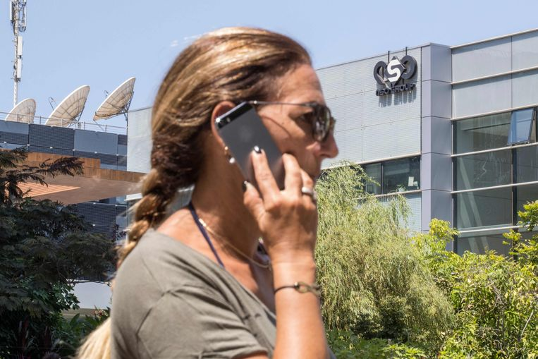 Vrouw met iPhone voor het Israëlische hoofdkantoor van Pegasus. Ook iPhones blijken gehackt te kunnen worden met de spionagesoftware van Pegasus. Beeld AFP