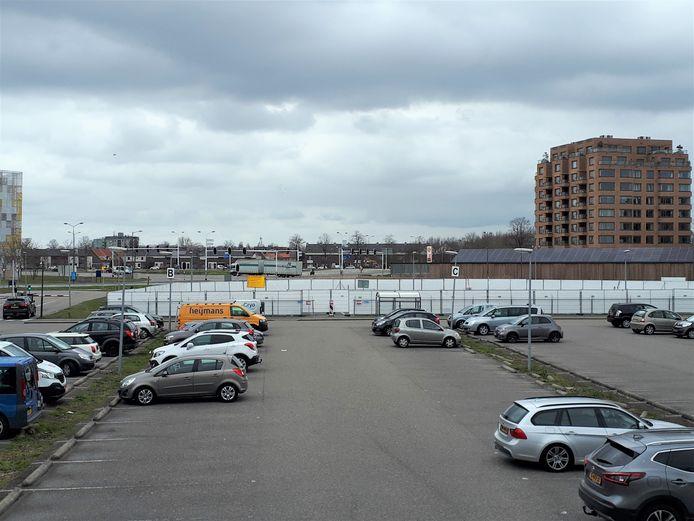 Geblindeerde hekken rondom een deel van het parkeerterrein.