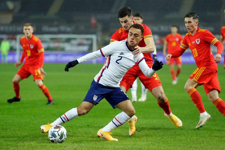 Sergino Dest van het Amerikaanse team (in wit) probeert de bal weg te houden bij Tom Lawrence van Wales.  Beeld AP