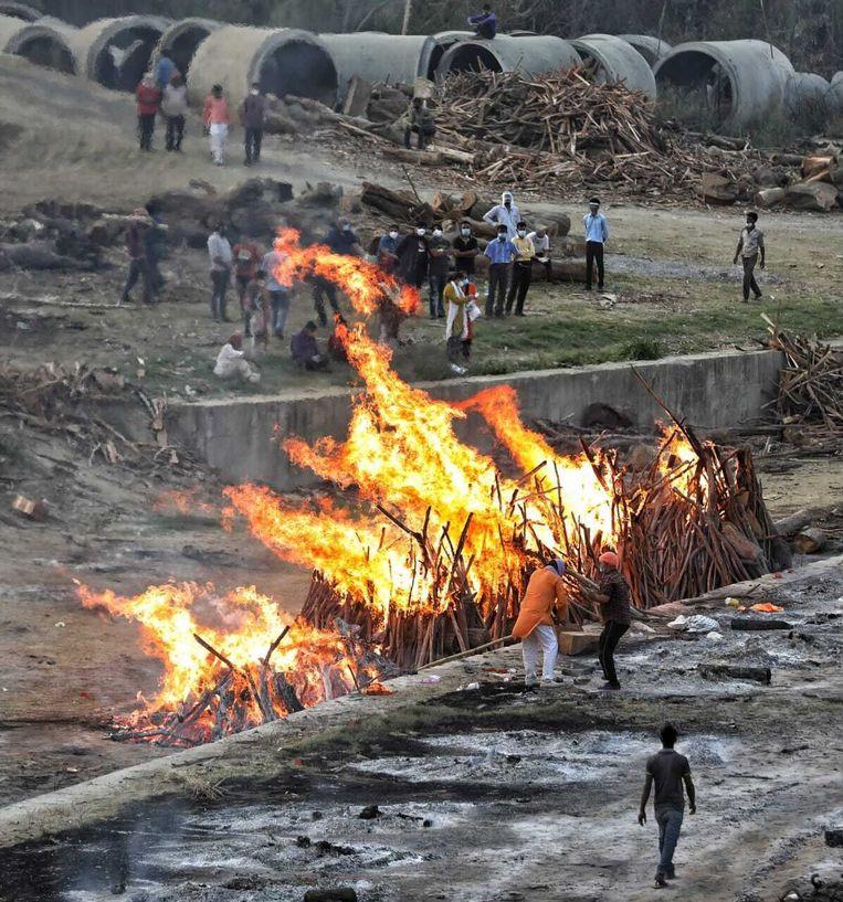 India wist niet te ontsnappen aan een zware, tweede coronagolf. In de Noord-Indiase stad Lucknow worden de coronadoden buiten op brandstapels gecremeerd. Beeld Saurabh Sharma