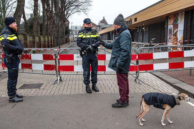 Politieagenten praten met een burger na een explosie bij een Poolse supermarkt in Beverwijk.  Beeld Guus Dubbelman / de Volkskrant