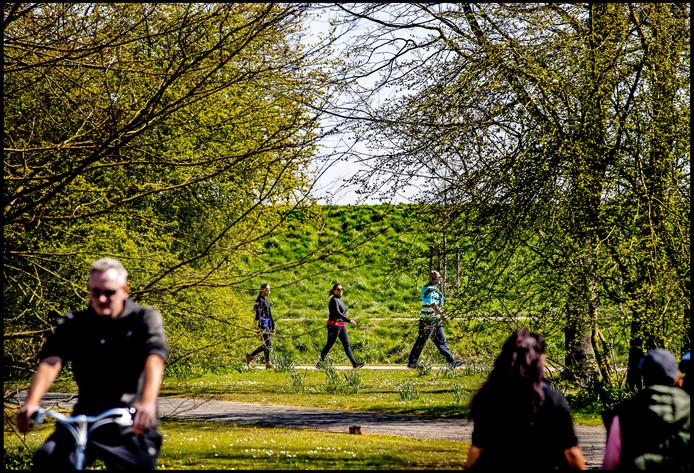 Mensen wandelen op anderhalve meter afstand van elkaar door het Haarlemmermeerse Bos . De fietsers genieten ook van het groen en het mooie weer.