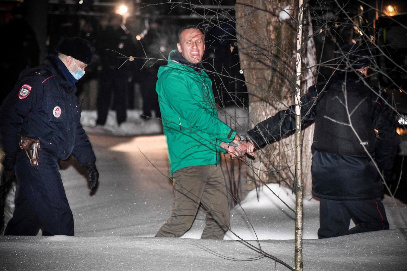 Alexei Navalny wordt begeleid door agenten.