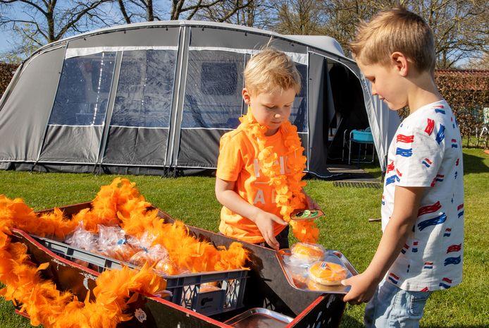 Vlnr: Naud Langers en Revi Langers delen op Koningsdag oranje donuts uit op mini-camping Gravenkasteel.
