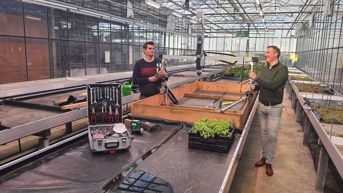 Etiënne Goossens van Curio en Bas Postma van Avans laten de farmrobot zien.