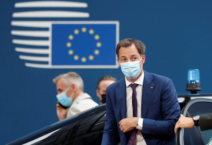 Premier Alexander De Croo bij aankomst in Brussel, met regenboogpin opgespeld.