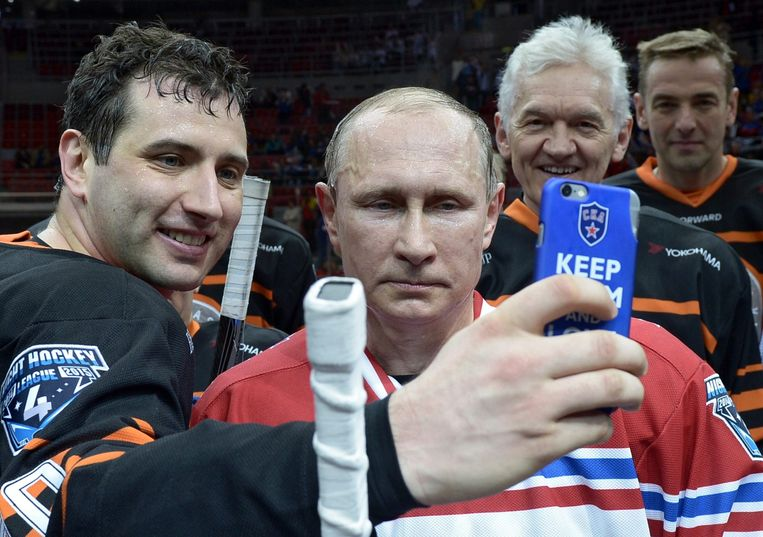 De Russische president Poetin (midden) poseert  voor een foto tijdens een ijshockeygala in Sotsji. Schuin achter Poetin, met het grijze haar, Gennady Timchenko. Beeld EPA