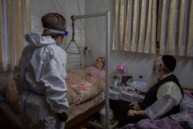 Een vrijwilliger van liefdadigheidsorganisatie Hasdei Amram verpleegt zieken thuis in de ultraorthodoxe wijk Mea Shearim. Beeld NYT