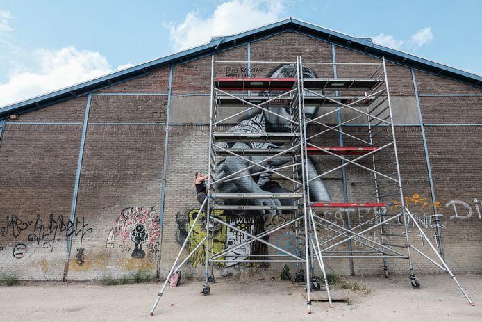 Kunstenares Rosalie de Graaf aan het werk in haar stadje Doesburg. Ze maakt een muurschildering op de oude GTW-loods.