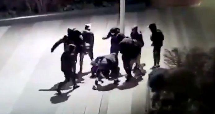 De groep jongeren staat rondom de op de grond liggende Yuriy.